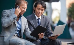 Businessmen using electronic gadgets